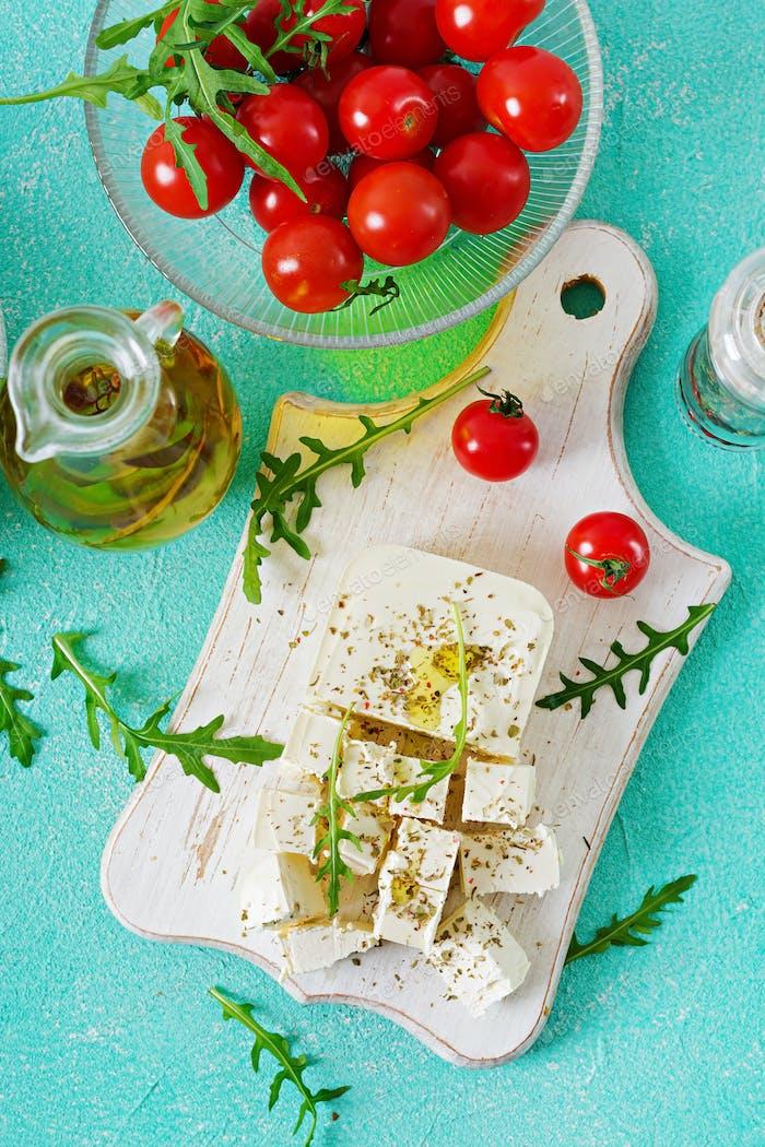 Feta-Käse, Kirschtomaten und Rucola auf dem Tisch. Zutaten für Salat. Ansicht von oben
