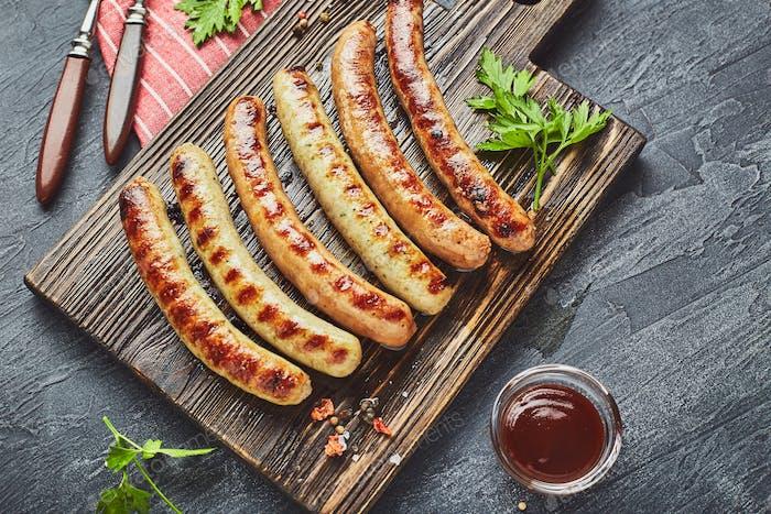 Leckere gegrillte Schweinefleisch Würstchen mit Gewürzen und Kräutern auf Holzschneidebrett in Nahaufnahme.