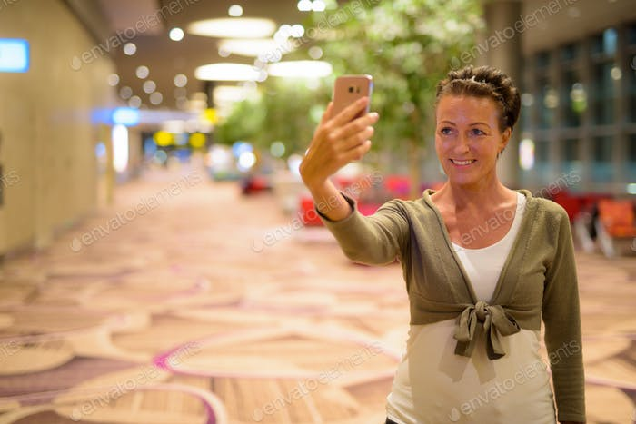 Happy mature beautiful tourist woman taking selfie at the lounge indoors