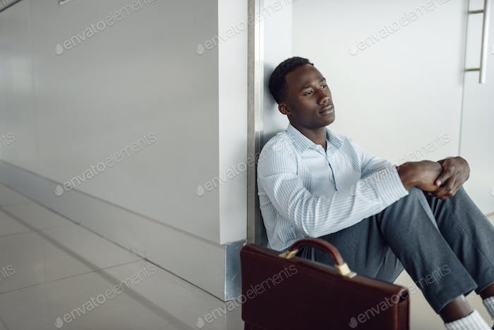 Businessman sitting on the floor in office hallway
