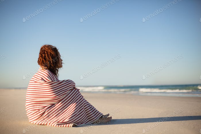 Side view of beautiful mixed race woman wrapped in blanket sitting on beach in the sunshine