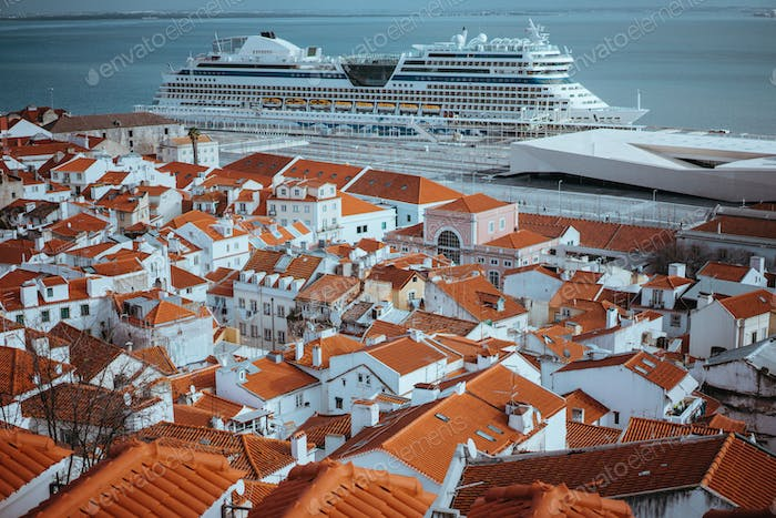 Rooftopspanorama of the oldest district Alfama in Lisbon. Cruise boat on the Tagus River. Lisbon