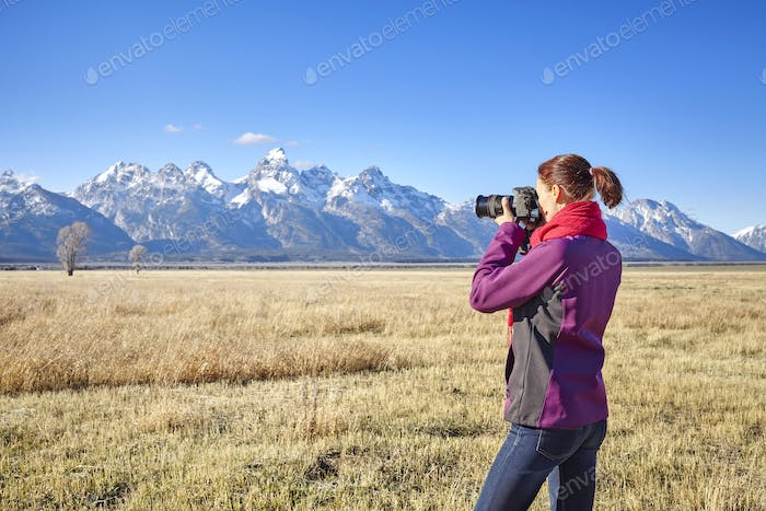 Female fit hiker taking pictures with DSLR camera in the Grand T