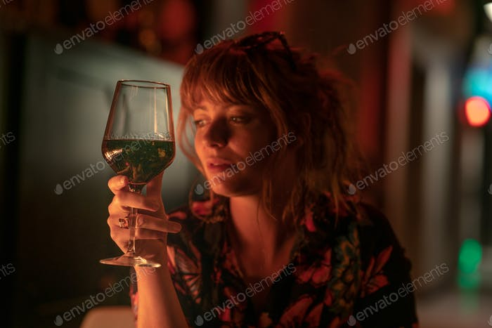 Glass of red wine with beautiful ginger girl holding