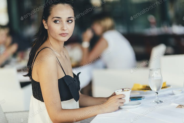 Attractive female drinking coffee from cup