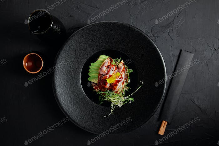 top view of Japanese Ceviche with seafood, avocado and herbs on black plate