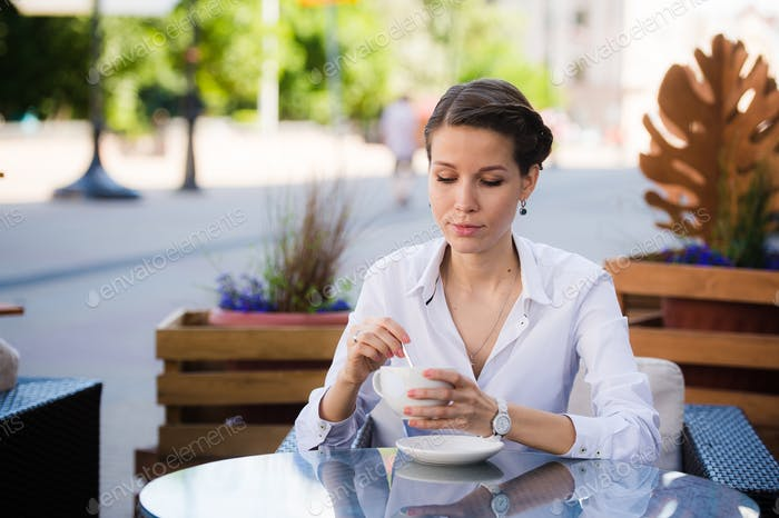 Modern young woman sitting in a cafe and waiting for someone looking to her watches