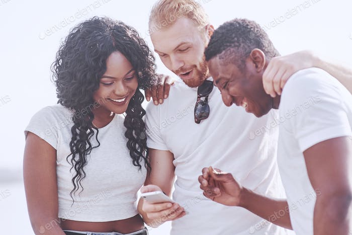 Group of multiracial happy friends using gadget outdoors. Concept of happiness
