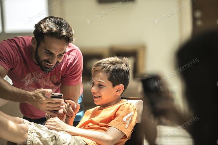 Ein Mann und ein Junge, der einen Handy-Bildschirm ansieht.