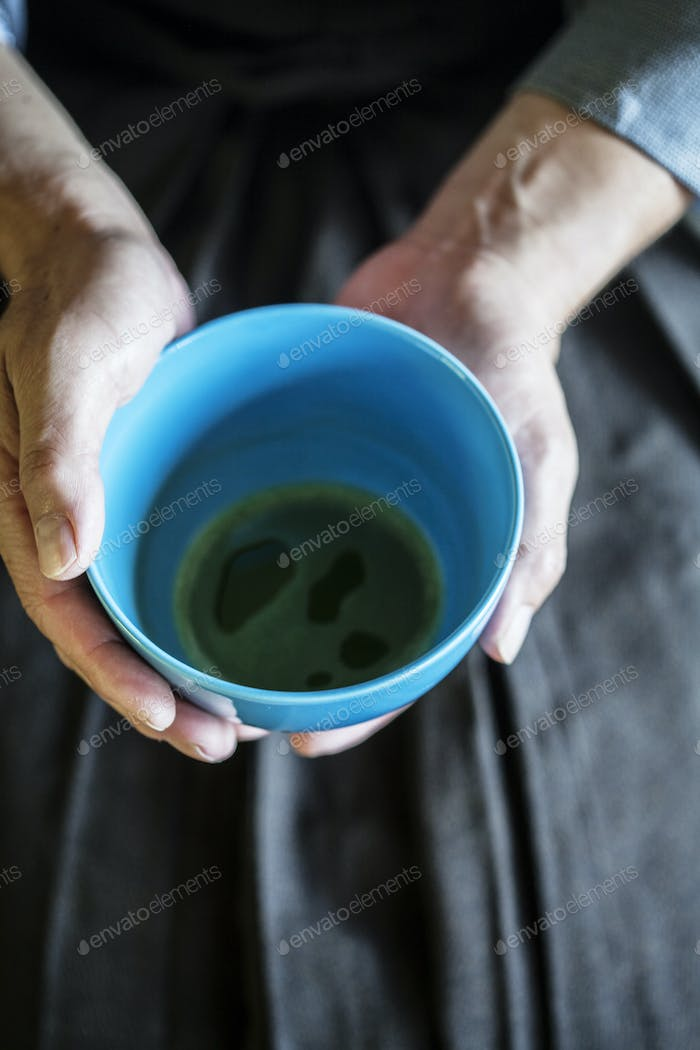 Man holding blue tea bowl during tea ceremony.