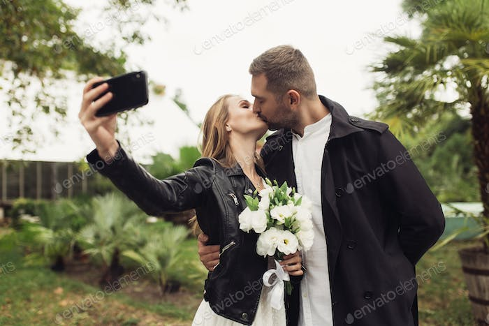 Young handsome man dreamily kissing beautiful woman in black lea