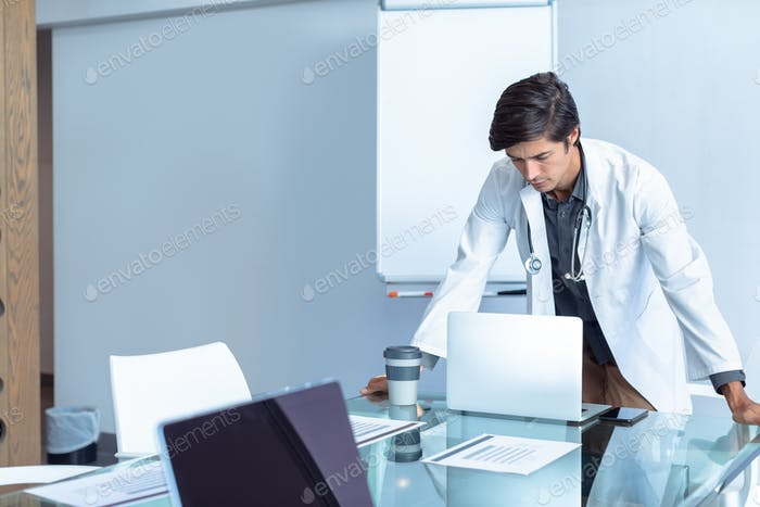 Male Caucasian doctor standing while using laptop at table l