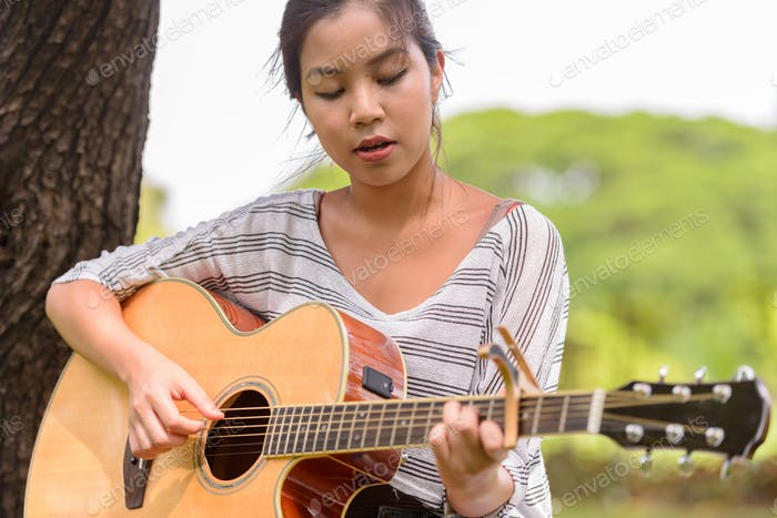Young beautiful Asian woman playing guitar at the park