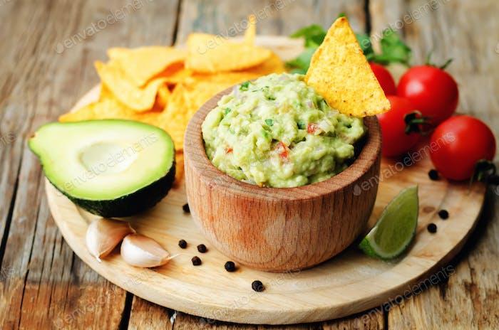 Guacamole mit Maischips und Zutaten, um es vorzubereiten