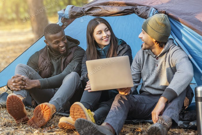 Three happy friends sitting in camping tent and using laptop