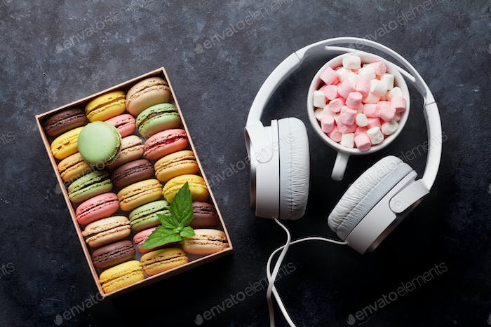 Colorful macaroons in a gift box and headphones