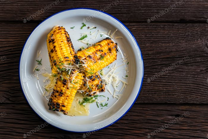 Top view grilled corn on the cob in white plate