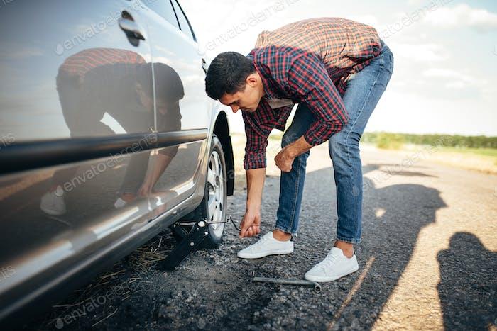 Man jack up broken car, wheel replacement