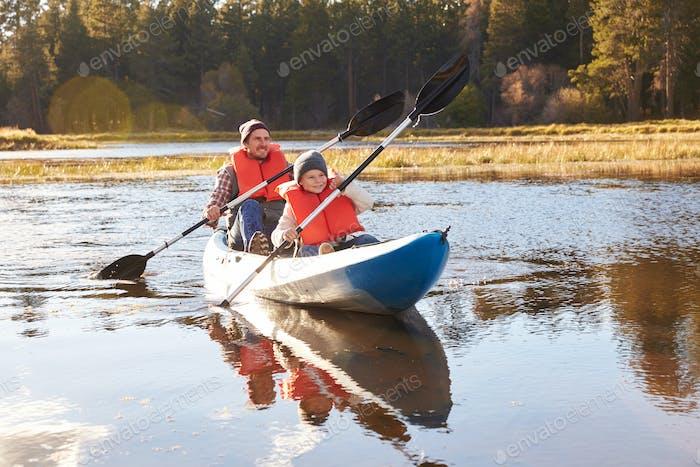 Father and son kayaking on lake, California, USA