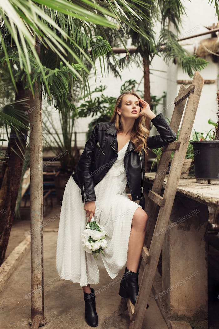 Young gorgeous woman in black leather jacket and white dress hol