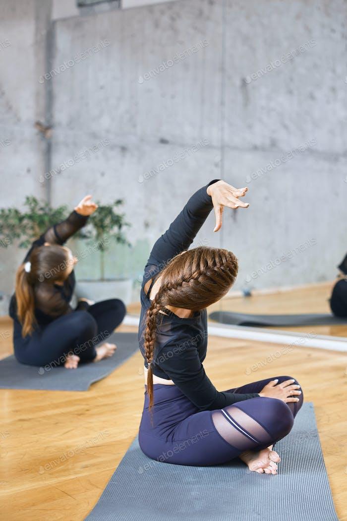 Women practicing practicing lotus pose in hall