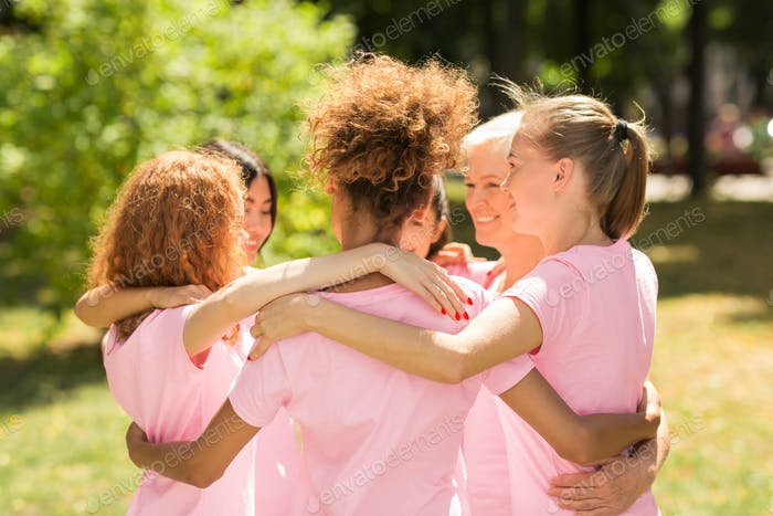 Women In Pink T-Shirts Hugging During Support Group Meeting Outdoor