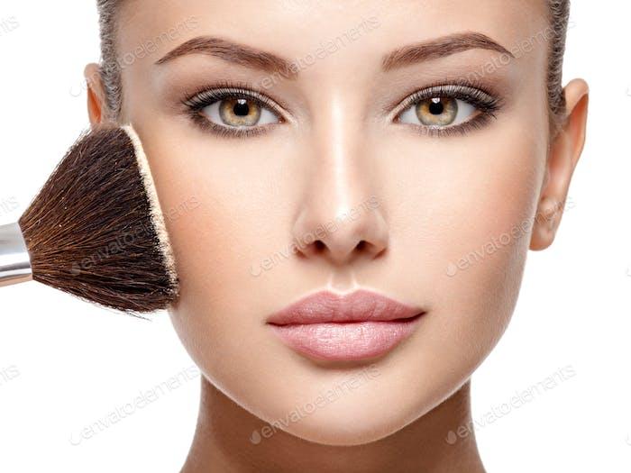 Frau Anwendung trockenen kosmetischen tonalen Fundament auf dem Gesicht