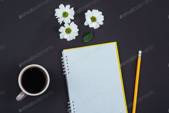 On a black background notebook pencil, fragrant coffee and white flowers.