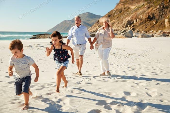 Senior weißes Paar und ihre Enkel zu Fuß an einem sonnigen Strand, Nahaufnahme