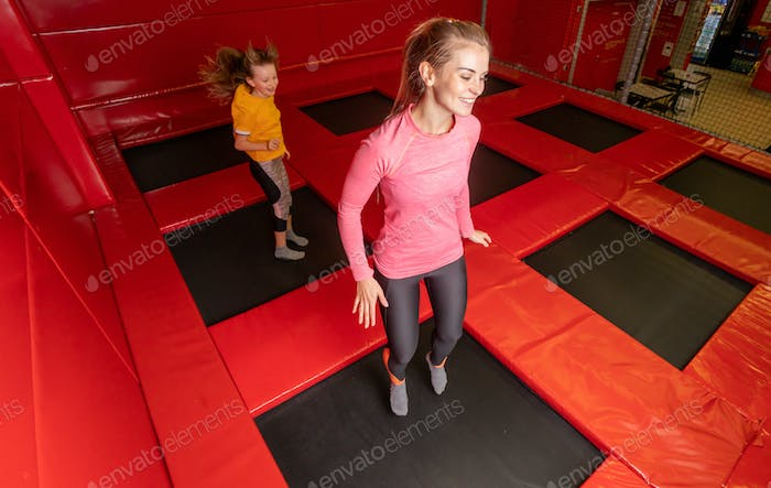 Happy family having fun while jumping on trampoline