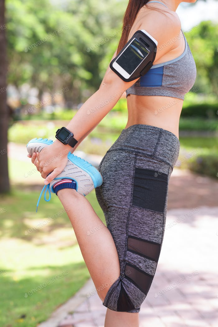 Woman with armband stretching in park
