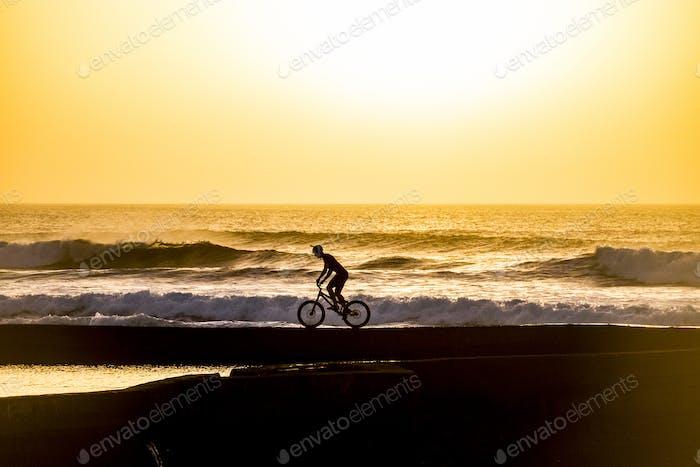 Silhouette eines männlichen Mountainbikers bei Sonnenuntergang am Meer - aktive Sportfahrer Menschen