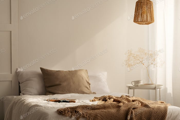 Closeup of bed with beige blanket and linen pillow in minimal be