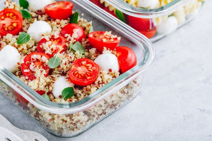 Vegetarian meal prep lunch box containers with quinoa, mozzarella, tomatoes and basil.