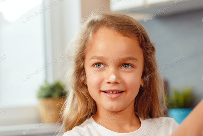 Portrait of a smiling little girl in kitchen
