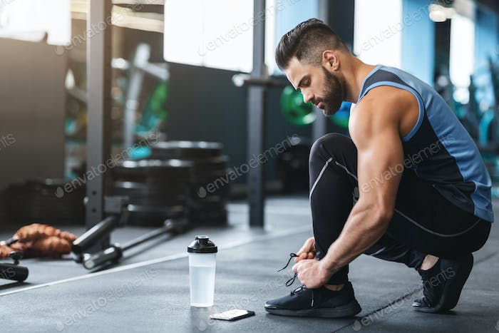 Young athlete tying sneakers laces at gym
