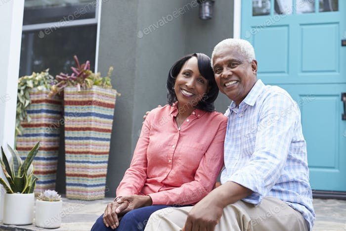 Senior couple sit on steps outside their house, close up