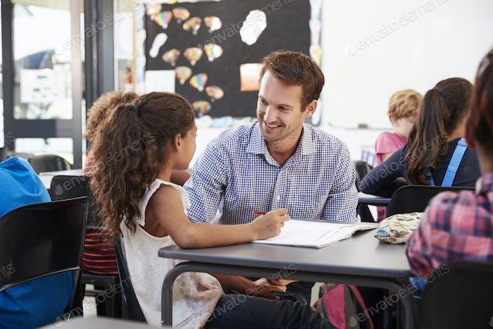 Lehrer und Schulmädchen an ihrem Schreibtisch, Blick auf einander
