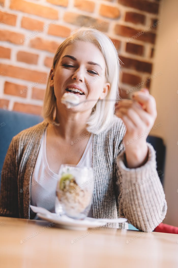 Woman eating fit meal with fruits and oats in a cafe.