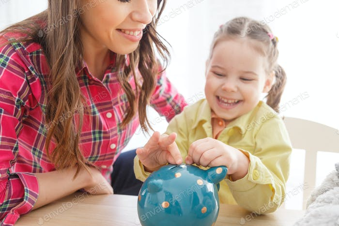 Child girl putting coin to piggy bank