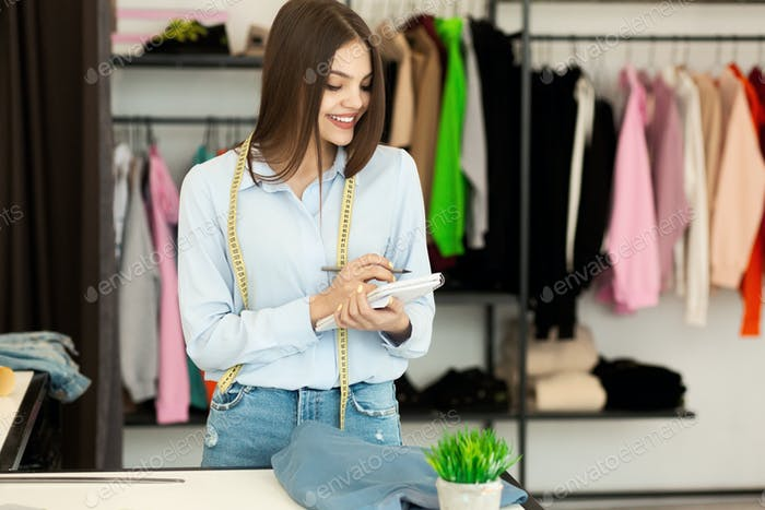 Clothing Designer Planning Incomes And Expenses In Fashion Showroom