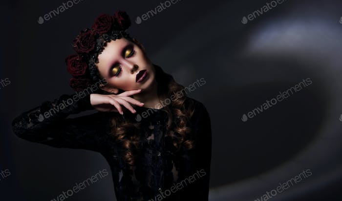 Dreamy woman with dark wreath of roses