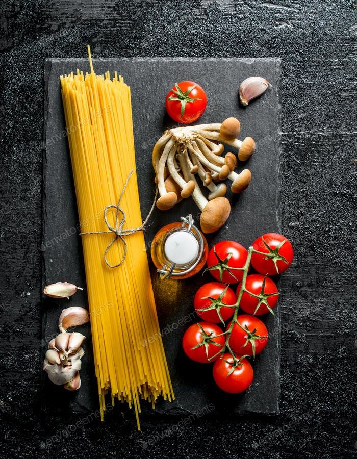 Raw spaghetti on black stone Board with tomatoes, garlic, mushrooms and oil.