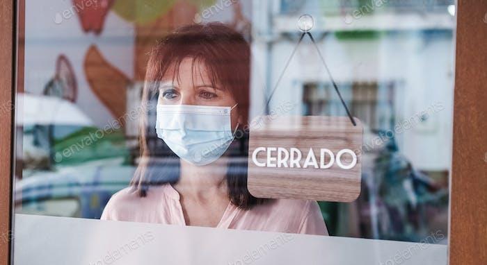 mujer triste con máscara de cara cambiando abierto a signo cerrado en español en la ventana para el virus corona