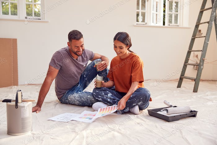 Couple Sitting On Floor With Paint Chart Ready To Decorate New Home