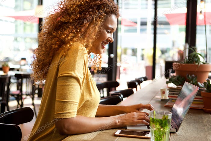 attractive young woman working with laptop at cafe