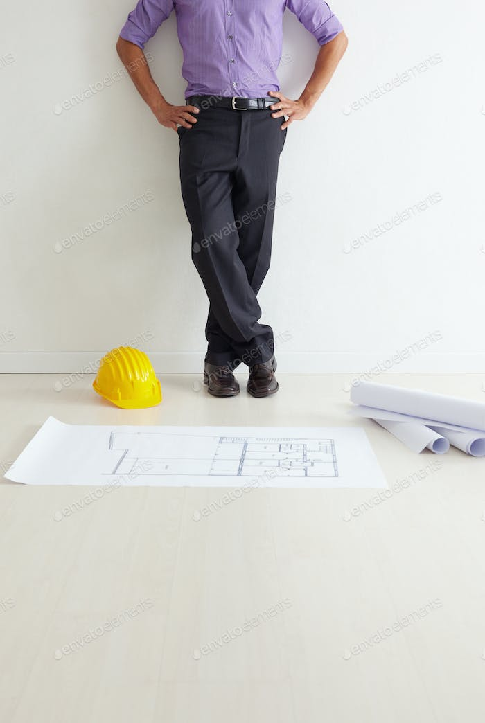 Male Architect Standing Near Blueprint Project Contemplating Plans
