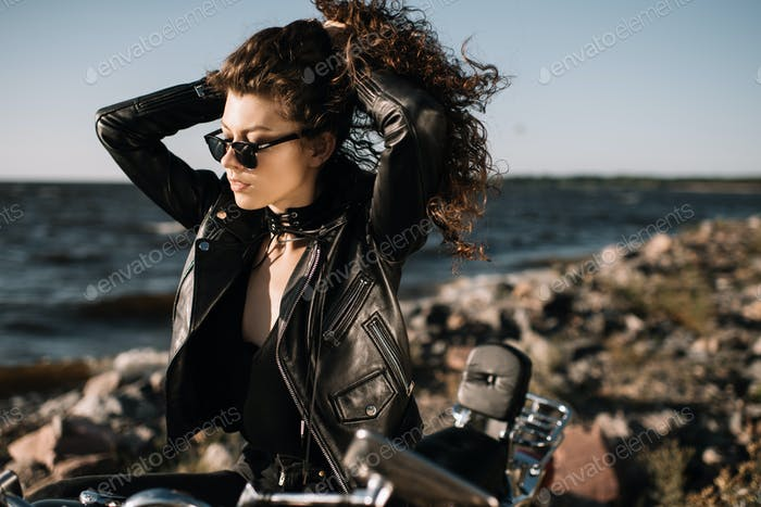 beautiful curly girl in sunglasses sitting on motorcycle
