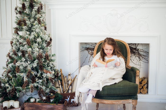 Little girl reading book near Christmas tree