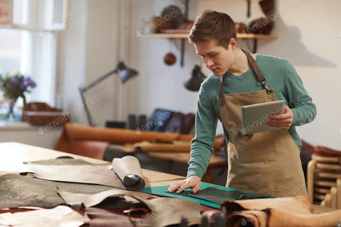 Male Artisan Choosing Piece Of Leather